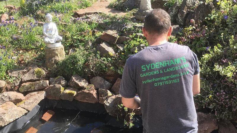 Sydenhams landscaper building rockery and pond in large garden